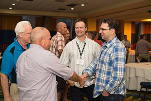 Group of men shaking hands at conference event