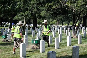 Three landscapers working hauling debris in a cemetary